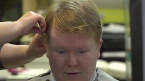 Молодой человек режет волосы в парикмахерской r видеоматериал