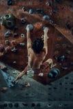 Молодой человек свободного альпиниста взбираясь искусственный валун внутри помещения Стоковые Фотографии RF