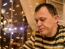 Молодой человек сидит в вечере в кафе около окна стоковое изображение