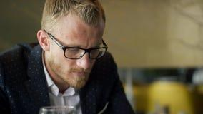 Молодой человек сидит в ресторане смотря телефон и разговаривает с персоной видеоматериал