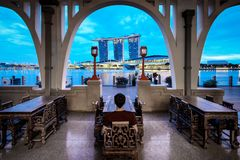 Молодой человек сидит и наслаждается взгляд песков залива Марины, Сингапур стоковое фото rf