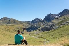 Молодой человек сидя вниз и смотря долина в Пиренеи стоковые изображения rf