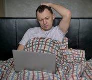 Молодой человек сидя в кровати под крышками с ноутбуком стоковые фотографии rf