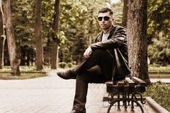 Молодой человек сидя в парке на стенде в солнечных очках и кожаной куртке стоковое изображение rf