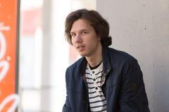 Молодой человек сидя и смотря камера стоковые изображения rf