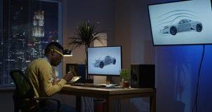 Молодой человек сидя назад и редактируя изображение на его компьютере акции видеоматериалы
