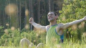 Молодой человек сидя на природе в жизни и усмехаться травы счастливых наслаждаясь сток-видео