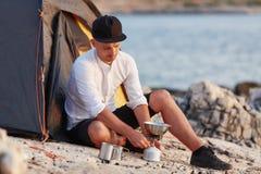 Молодой человек сидя на скалистом seashore около шатра, устанавливая плитку газа стоковые изображения