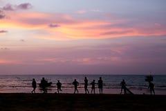 Молодой человек силуэта играя футбол пляжа Стоковая Фотография RF
