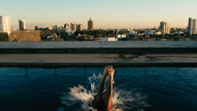 молодой человек скача к бассейну на крыше над городом стоковые фотографии rf