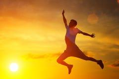 Молодой человек скачет к верхней части на предпосылке захода солнца стоковые изображения