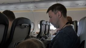Молодой человек слушая к музыке на наушниках через сотовый телефон Бизнесмен во время полета наблюдает видео от a акции видеоматериалы