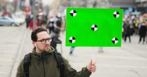 Молодой человек смотрит плакат с зеленым экраном в его руке на ралли города акции видеоматериалы