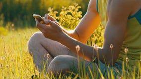 Молодой человек смотрит smartphone и что-то печатает на зеленой траве против фона красивого лета видеоматериал