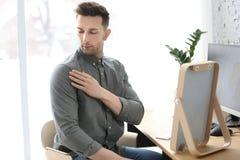 Молодой человек смотря перхоть в его плече стоковое фото
