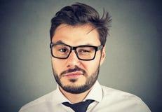 Молодой человек смотря с недовериями надоел с ситуацией стоковая фотография