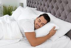 Молодой человек спать в кровати с мягкими подушками стоковое изображение rf