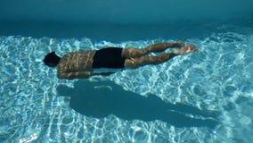 Молодой человек спорта при тонизированное тело плавая под водой в бассейне с кристаллом - чистой водой сезон лета на тропической  сток-видео
