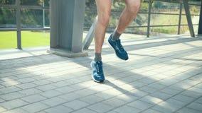 Молодой человек спортсмена в веревочке удобного обмундирования спорта скача на спортивной площадке на платформе около шкафов мета сток-видео