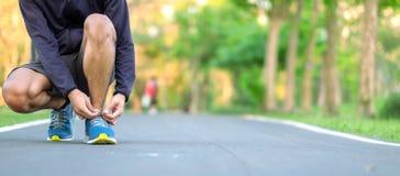 Молодой человек спортсмена связывая ботинки бега в парке на открытом воздухе, мужской бегуна готовый для jogging на дороге снаруж стоковые фотографии rf