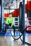 Молодой человек спортсменов делает тренировки на спортзале изолированная принципиальной схемой белизна спорта стоковое фото