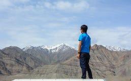 Молодой человек стоит на горе стоковые фото