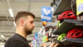 Молодой человек стоит около стойки в магазине велосипеда Выбор шлема велосипеда в небольшом магазине видеоматериал