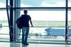 Молодой человек стоящее близко окно на авиапорте и наблюдая pl стоковые изображения rf