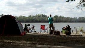 Молодой человек стоя в лагере на шатре предпосылки туристском и стульях на реке банка сток-видео