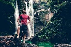 Молодой человек стоя около водопада в лесе Стоковое Фото