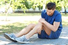 Молодой человек страдая от боли в ноге Стоковые Изображения