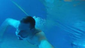 Молодой человек с атлетическим телом плавает под водой видеоматериал