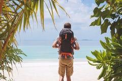 Молодой человек с большим рюкзаком идя к пляжу в тропическом назначении праздника стоковые фотографии rf