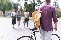Молодой человек с велосипедом и рюкзаком стоковое изображение