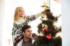 Молодой человек с его дочерью на его плечах помогая ее decorat стоковое изображение