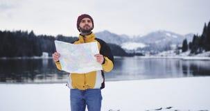 Молодой человек с картой проверяя его положение, он идя перед камерой вокруг озера берега и смотря вокруг акции видеоматериалы