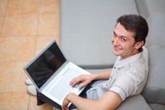 Молодой человек с компьтер-книжкой на софе стоковая фотография rf