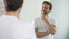 Молодой человек с красивыми спорт вычисляет рассматривать его отражение в зеркале видеоматериал