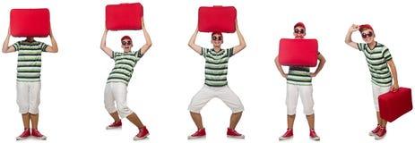 Молодой человек с красным чемоданом изолированным на белизне стоковые фотографии rf