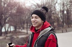Молодой человек с мобильным телефоном в парке города стоковые фотографии rf