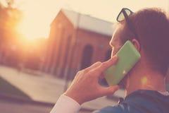 Молодой человек с мобильным телефоном имеет переговор, заход солнца на улице стоковое фото rf
