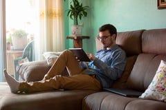 Молодой человек с планшетом на софе дома стоковые фотографии rf