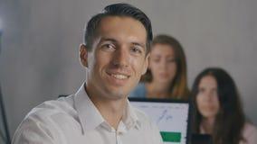 Молодой человек с портретом стекел глаза усмехаясь Встреча офиса работы команды корпоративного бизнеса акции видеоматериалы