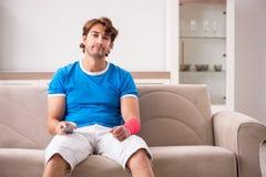 Молодой человек с раненой рукой сидя на софе стоковое изображение
