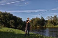 Молодой человек с рыболовной удочкой на реке в Германии Стоковое Изображение