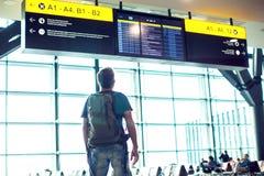 Молодой человек с рюкзаком в авиапорте около расписания полета Путешествия стоковое изображение rf