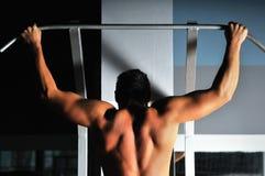 Молодой человек с сильными рукоятками разрабатывая в гимнастике Стоковое Изображение