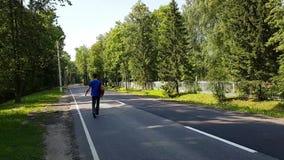 Молодой человек с хромые прогулки вдоль дороги С рюкзаком на его плечах Путешествовать самостоятельно взрослое акции видеоматериалы