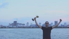 Молодой человек с чашкой в его руках на вечере города Концепция как победа, успех и чемпион видеоматериал