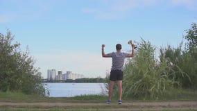 Молодой человек с чашкой в его руках радуется в победе спорт Танцы и скачки на городе вечера Концепция как победа сток-видео